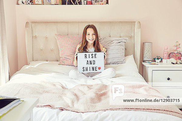 Girl holding up sign in bed