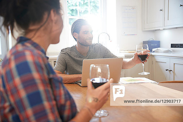 Couple at kitchen table drinking red wine while using laptop