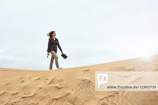 Female tourist walking barefoot on sand dune  Las Palmas  Gran Canaria  Canary Islands  Spain