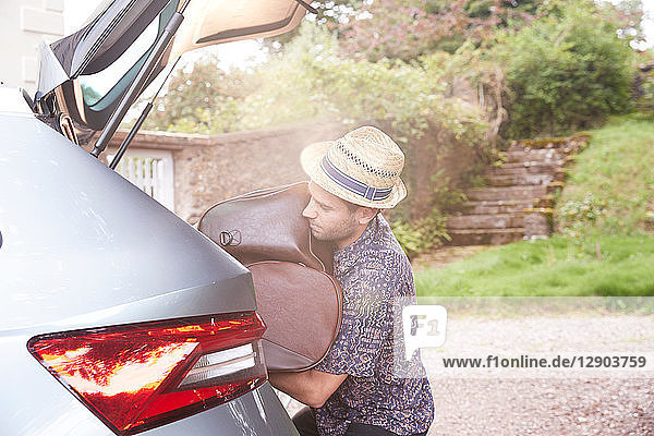 Young man in trilby removing luggage from car boot outside hotel