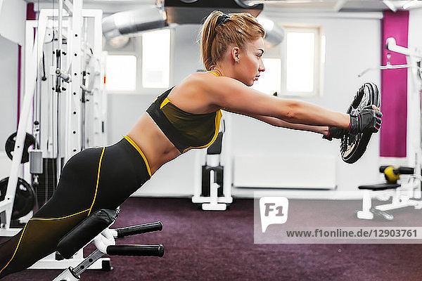 Frau hebt Gewichtsscheibe und beugt sich im Fitnessstudio vor