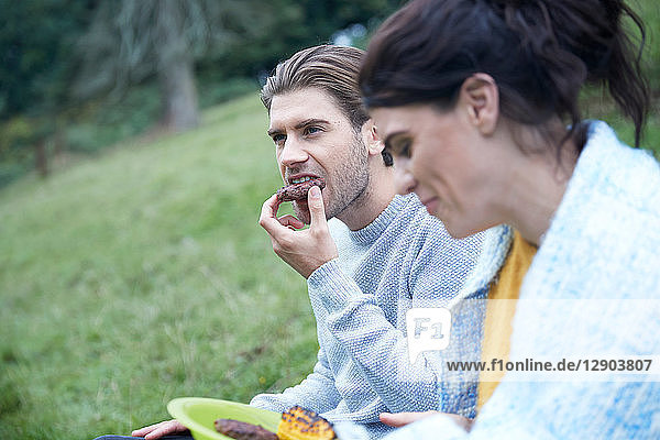 Couple sitting in rural field eating barbecue food