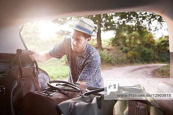 Young man in trilby removing luggage from car boot on rural road
