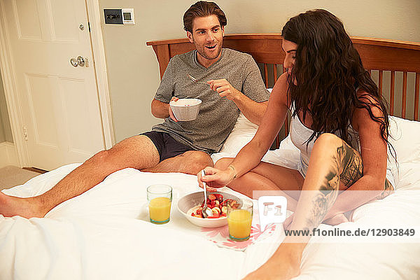 Couple sharing fruit and orange juice breakfast in bed