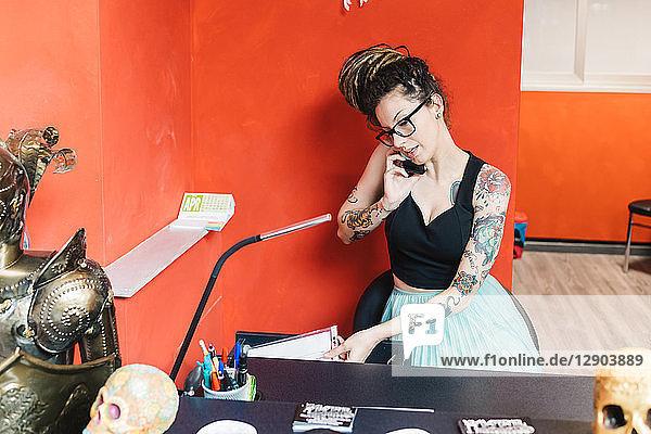 Tätowierer telefoniert mit Handy im Salon