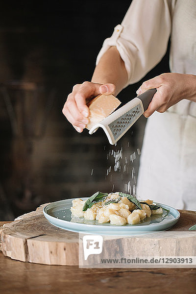 Potato gnocchi on plate being garnished