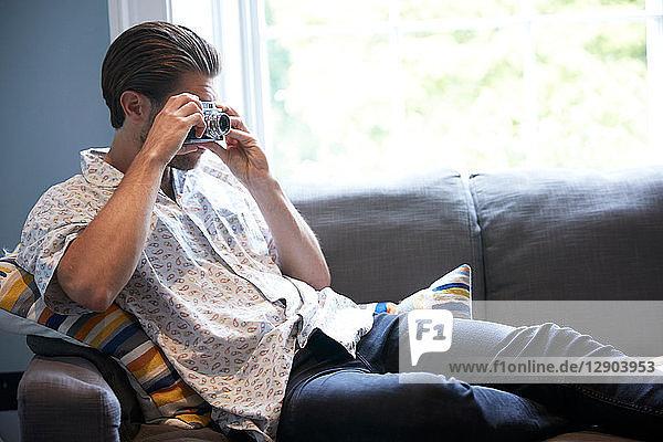 Man using camera on sofa