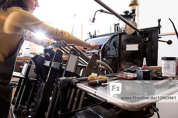 Woman preparing printer in shop