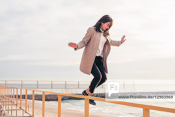 Frau springt am Strand vom Geländer