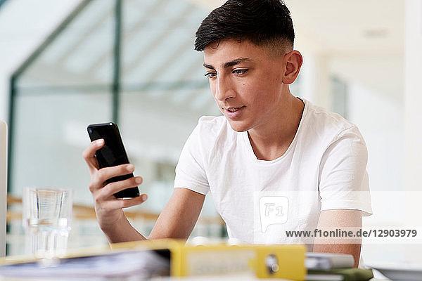 Teenager-Schüler am Schreibtisch im Klassenzimmer mit Blick auf Smartphone