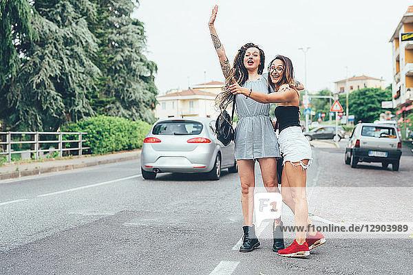 Freundinnen  die mitten auf der Straße ein Taxi anhalten