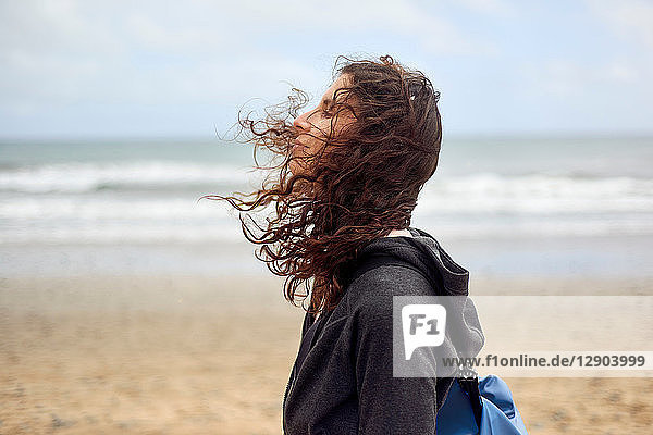 Female tourist with flyaway hair on beach  Las Palmas  Gran Canaria  Canary Islands  Spain