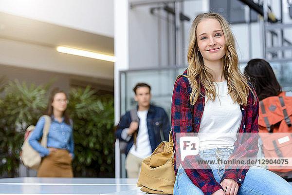 Young female university student sitting in university lobby  portrait