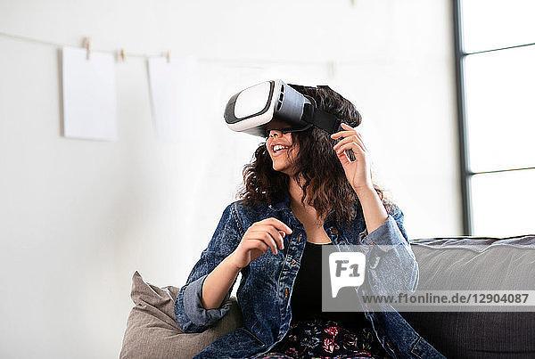 Teenager-Mädchen auf dem Sofa schaut durch ein Virtual-Reality-Headset
