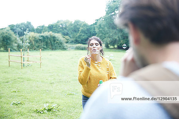 Couple playing with soap bubbles in field