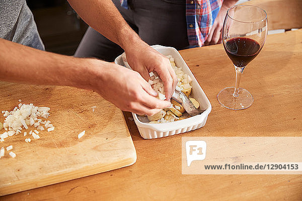 Couple putting vegetables in roasting dish at kitchen table  close up of hands