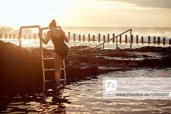 Woman climbing up coastal pool ladder  Las Palmas  Gran Canaria  Canary Islands  Spain