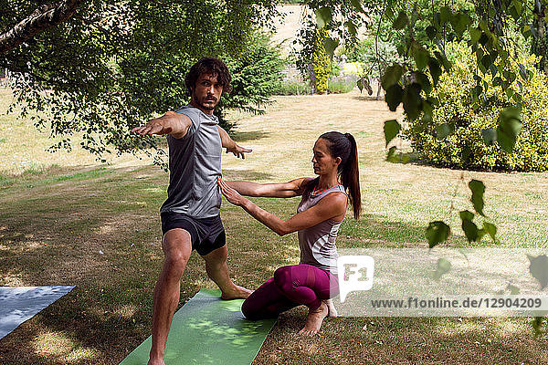 Female yoga teacher teaching young man yoga in garden  warrior pose