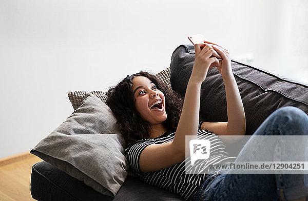 Teenagerin entspannt sich auf Sofa und lacht über Smartphone