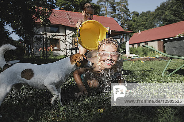Brother,  sister and dog playing with water in garden