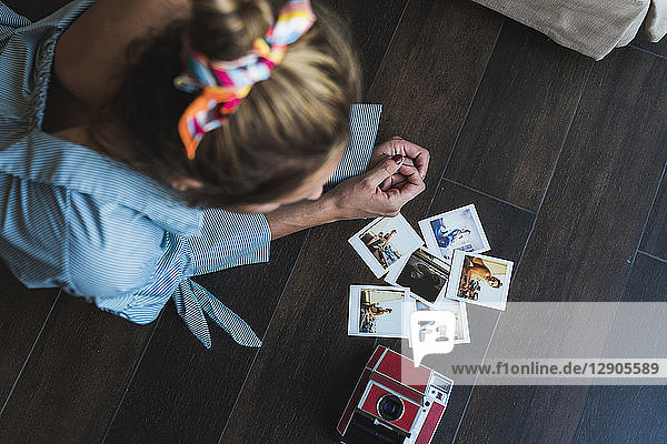 Young woman lying on the floor looking at instant photos of herself