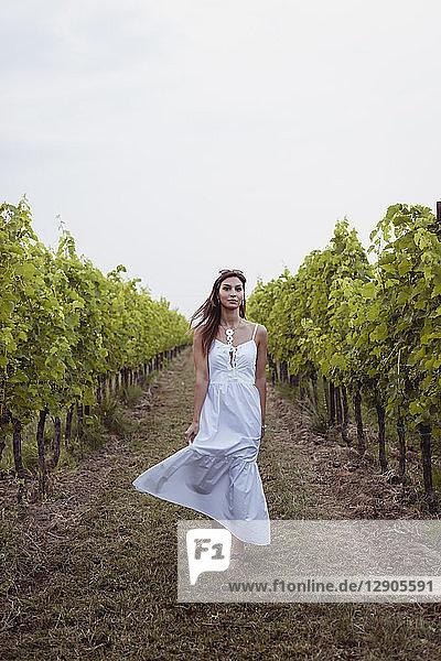 Woman wearing white summer dress  dancing in vineyard