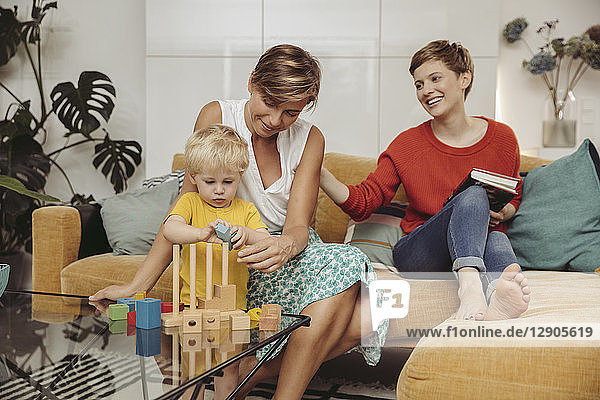 Two mothers learning and playing with their child at home
