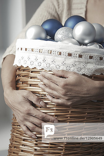 Woman carrying basket full of Christmas baubles