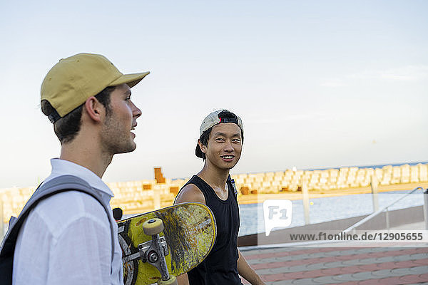 Two young men with skateboard on the move talking