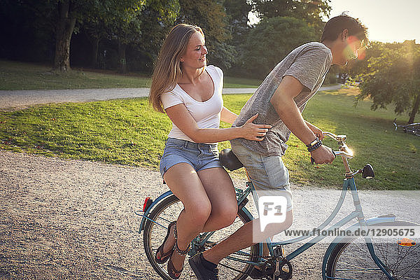 Young couple riding bicycle in park  woman sitting on rack