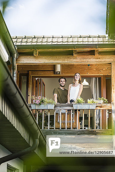 Smiling couple standing on balcony at home