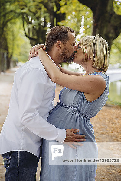 Mature pregnant couple kissing in park