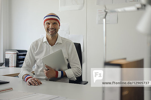 Businessman sitting in office  wearing sweat bands  holding laptop