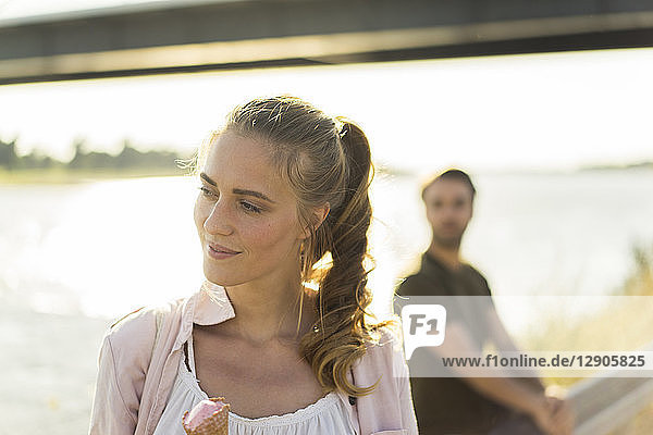 Woman eating ice cream in summer at the riverside with man in backgound