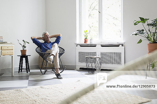 Relaxed mature man sitting at home