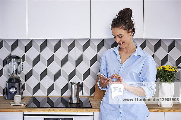 Young woman preparing coffee in the morning  using smartphone