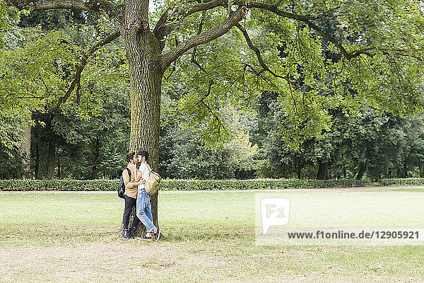 Kissing young gay couple leaning against tree in city park