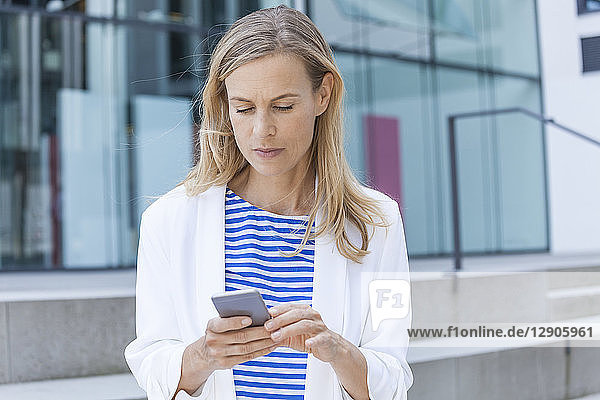 Smiling blond businesswoman using smartphone