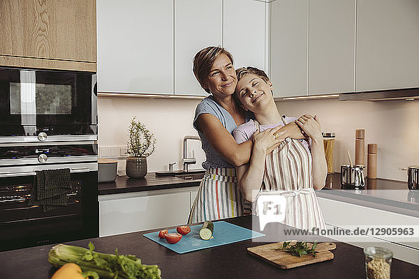 Happy lesbian couple standing in kitchen with aprons