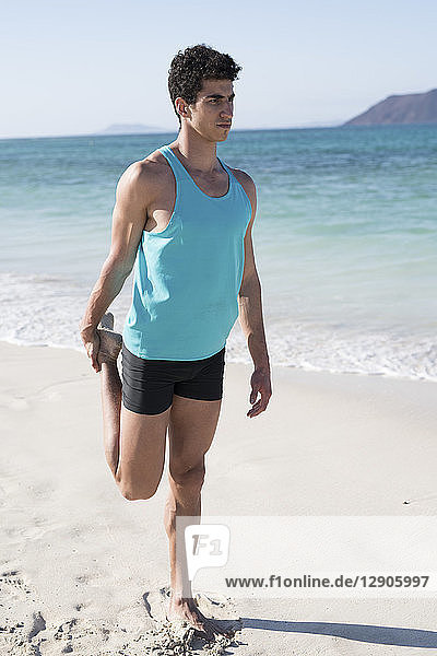 Spain  Canary Islands  Fuerteventura  young man stretching his leg on the beach
