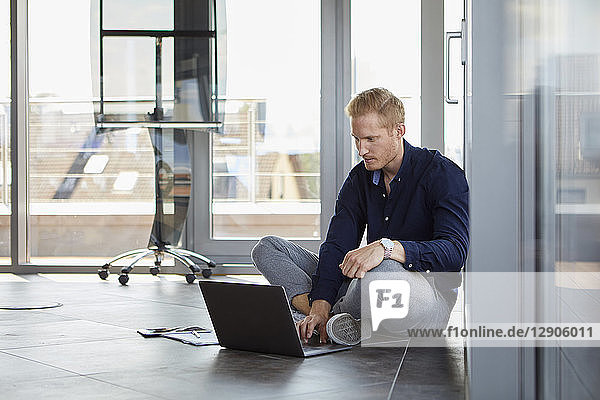 Businessman sitting on the floor using laptop