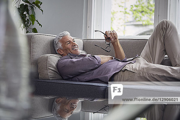 Smiling mature man lying on couch at home