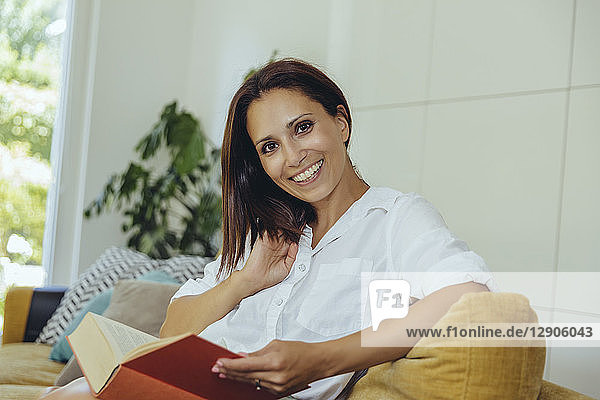Portrait of smiling woman reading book on couch