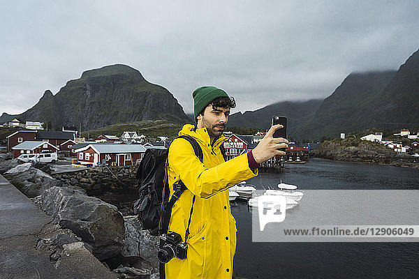 Norway  Lofoten  young man in a fishing village at the coast taking a selfie