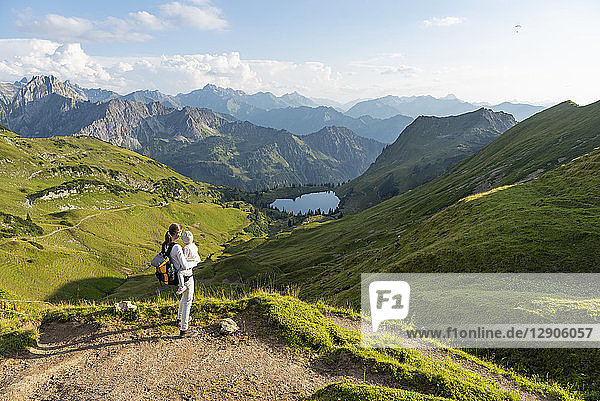 Germany  Bavaria  Oberstdorf  mother and little daughter on a hike in the mountains looking at view