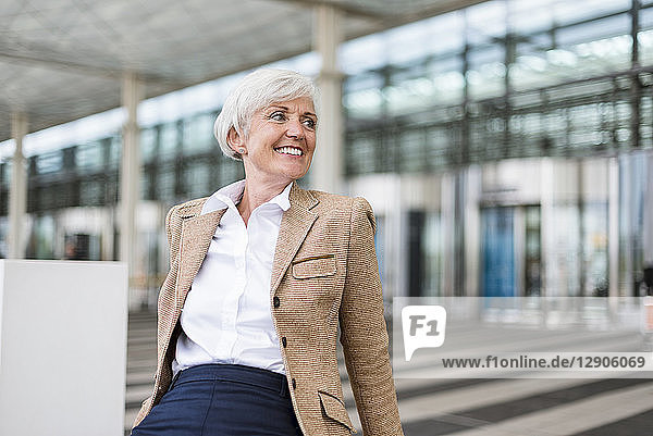 Smiling senior businesswoman sitting in the city looking around