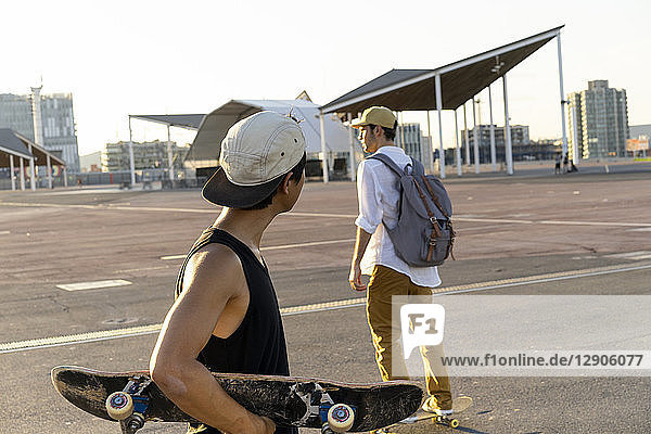 Two young men with skateboards on a parking level