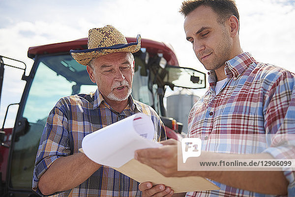 Two farmers discussing data from clipboard on the farm