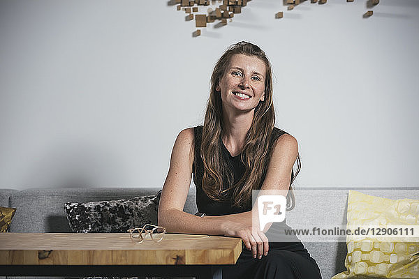 Woman sitting in modern office space  smiling