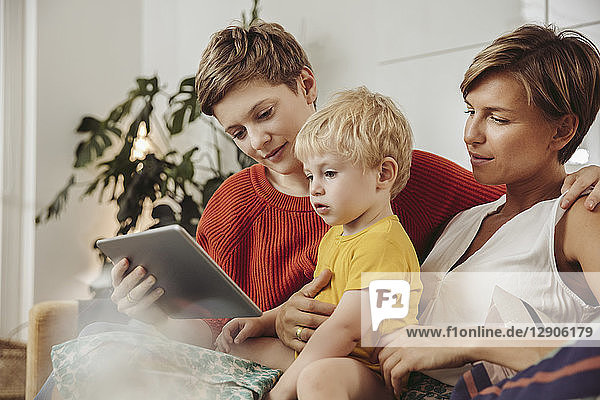 Two mothers looking at a tablet computer with their child at home